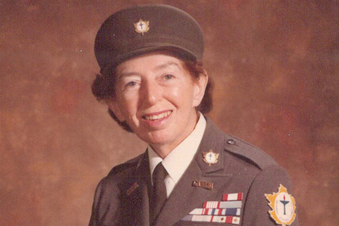 Biography of Lotta Hitschmanova reveals a life of service. In this portrait of Lotta, she's well into her career as the founder and leader of SeedChange. She smiles to the camera, wearing a military style cap and uniform.