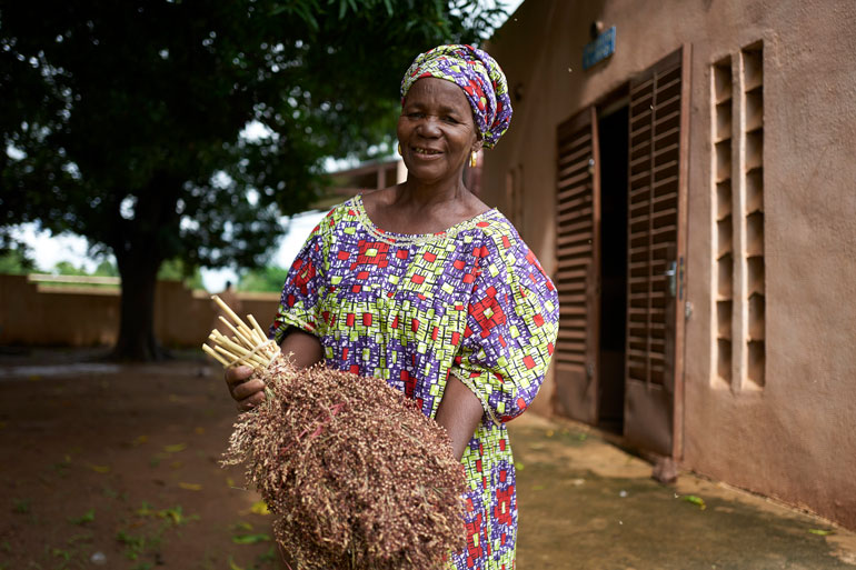 Sitan Diarra is a rural woman farmer in the Global South in Mali. In this image, she stands in front of a building holding a bundle of sorghum in her arms. Her dress and head wrap are colourful and she smiles looking directly into the camera.