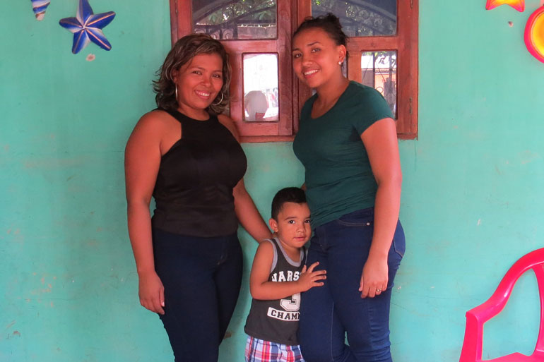 This image of two grown women and a young child standing in front of a brightly coloured wall. The two women are smiling and the child clutches one woman's leg with a small smile on his face.
