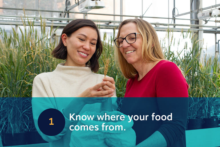 Five food resolutions for 2021, resolution 1: Know where your food comes from. Image of two women looking at a single stem of wheat held by the woman on the left. They both smile.