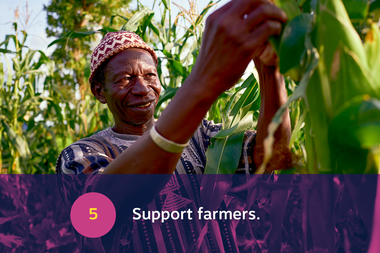 Five food resolutions for 2021, resolution 5: Support farmers. Image of a man in his field of maize. He is reaching up and holding one of the corn plants. He smiles toward the corn.