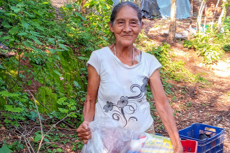 Donors respond to emergency need in Nicaragua: An woman with her hair tied back and a small smile on her face holds a translucent bag of goods.