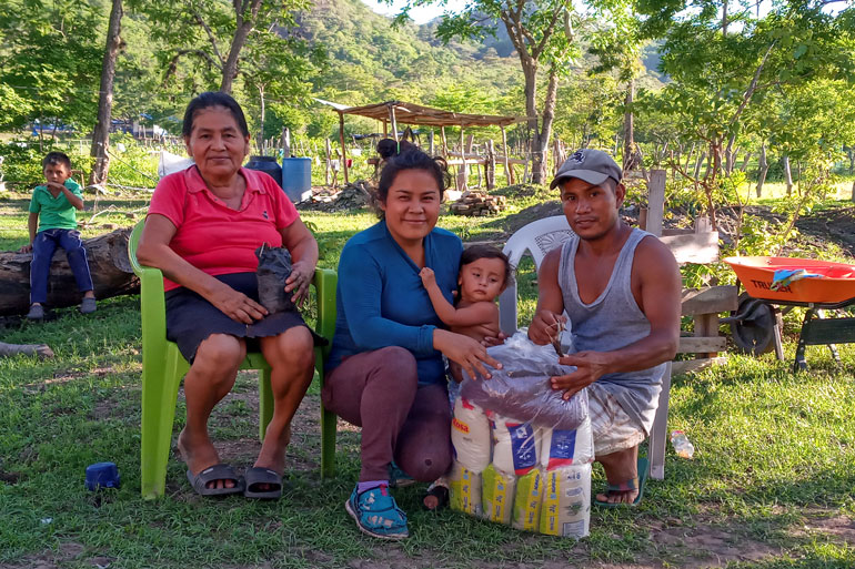 Donors respond to emergency need in Nicaragua: Three adults and a baby are together. On the left, an older woman sits in a plastic chair. Two younger adults crouch on the ground with the baby and smile toward the camera.