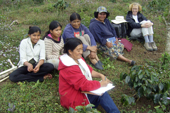 Six women sit on a grassy slope, smiling. The woman in the foreground is writing on paper held on a clipboard.