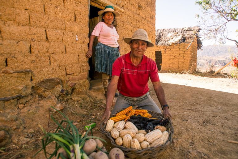 One farmer in jeans and a collared short-sleeved shirt crouches on the ground of packet dirt. He grips a basket full of different coloured corn cobs and smiles at the camera. A second farmer is walking out the a doorway behind him. She wears a wide-brimmed hat, a short sleeved shirt, a knee-length skirt with a velour-like texture and tall patterned socks. She is looking at the farmer crouched on the ground and seems to be in the middle of saying something.