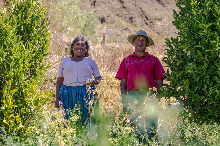 Two smiling people stand in a field among crops and bushes. They're stand proudly with smiles on their faces.