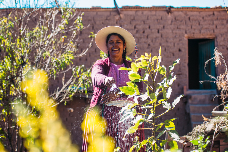 Image of woman farmer spraying water on crops. She's smiling and looking at the crops. A limestone wall in behind her.