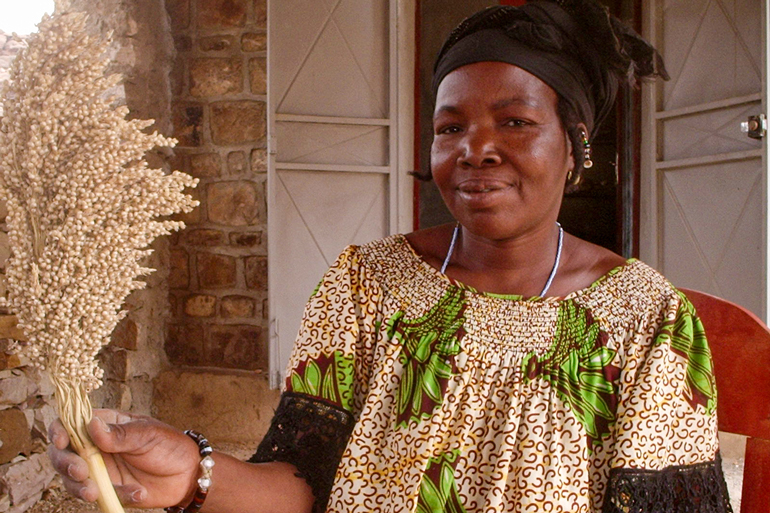 Aissata Ongoïba is a seed saver in Mali. She smiles toward the camera, holding a panicle of sorghum in her right hand. She is sitting.