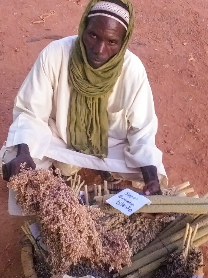A man squats on the ground next to a bin full of sorghum and millet packets. The packets are held together with string and are labeled with paper.
