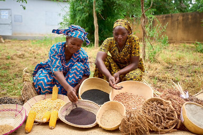 Two women crouch in the yard of a building behind baskets and bowls filled with seeds of many kinds.
