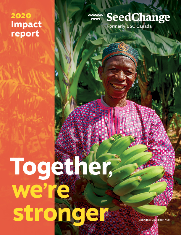 SeedChange annual impact report for 2020 cover features a photo of a man smiling widely into the camera. He's standing in front of a row of lush banana trees and holds a large bundle of banana in his hands.