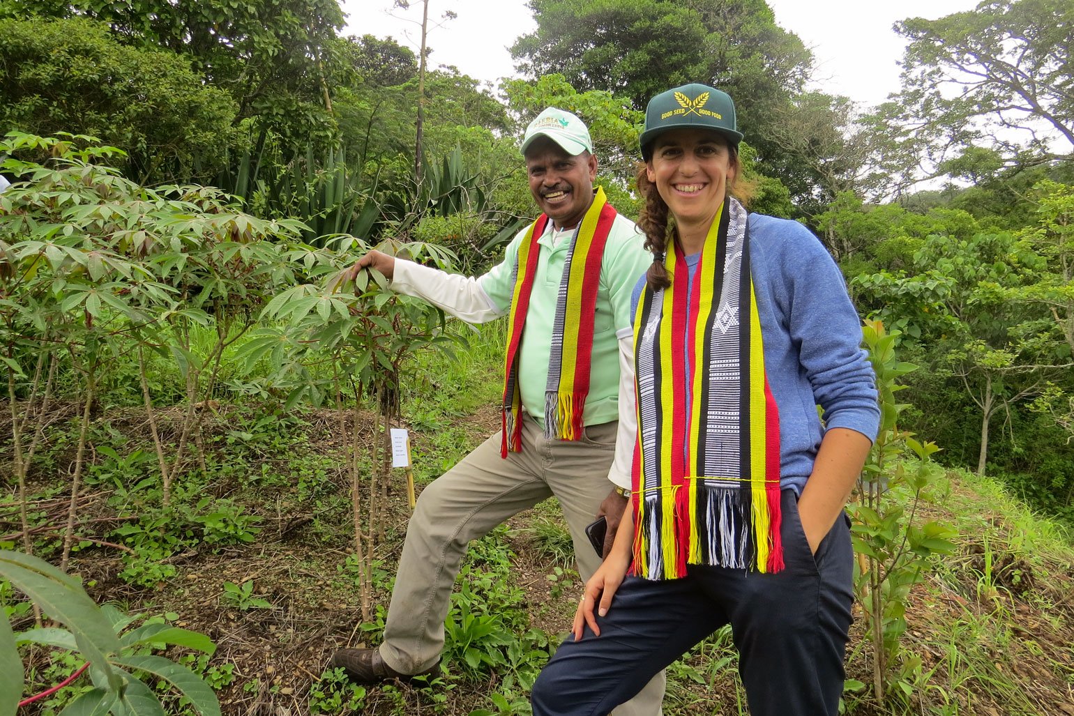 A man and a woman smile at the camera while standing in a sloped farm field where bushes, trees and smaller crops are growing.