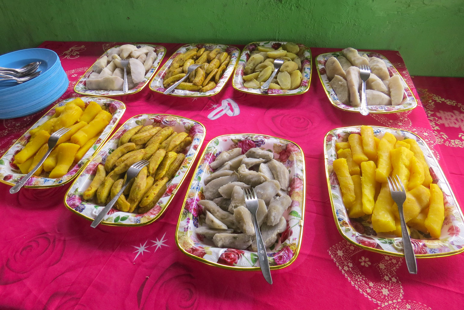 Where is cassava from? - Table covered in a red table cloth has eight trays on it, each containing root vegetables in white, grey and yellow.