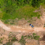 Agriculture, biodiversity loss and climate change - aerial shot of a tractor on a swath of deforested ground.