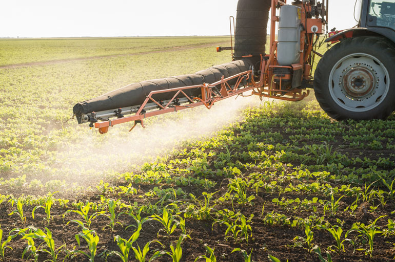The front tire and front spray piece of a tractor driving over a field and spraying a mist onto small crops below.