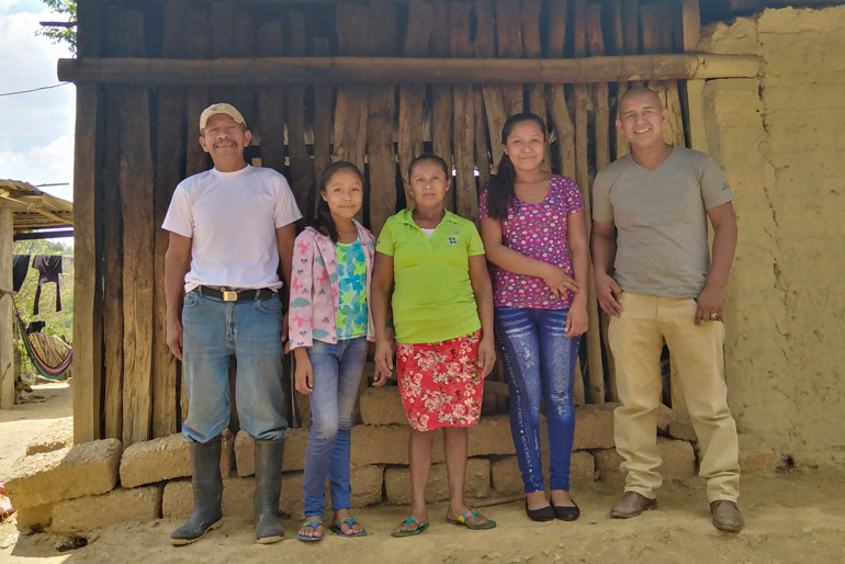 Farmers working together to resist market exploitation in Nicaragua - A family of five stands in front of an outdoor wall made of wood. They all look toward the camera and smile to varying degrees.