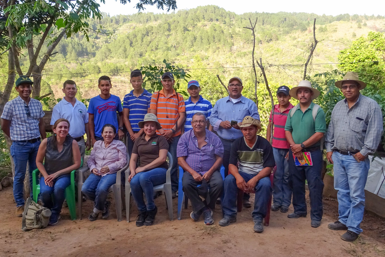Farming through hardship: A family farmer in Honduras discusses COVID, hurricanes and more - group photo of 15 people. The background is a mountain side.