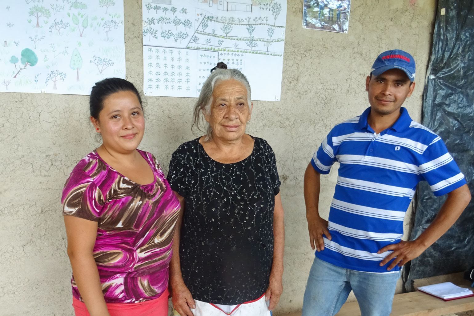 Farming through hardship: A family farmer in Honduras discusses COVID, hurricanes and more - A photo of three people standing in front of a concrete wall.